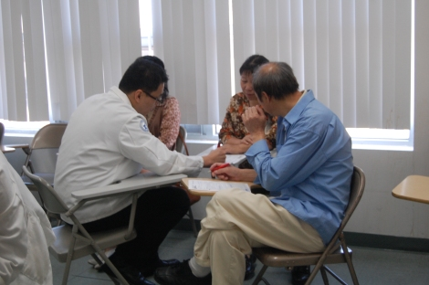Touro College of Pharmacy student William Loi reviewing the forms with the community members